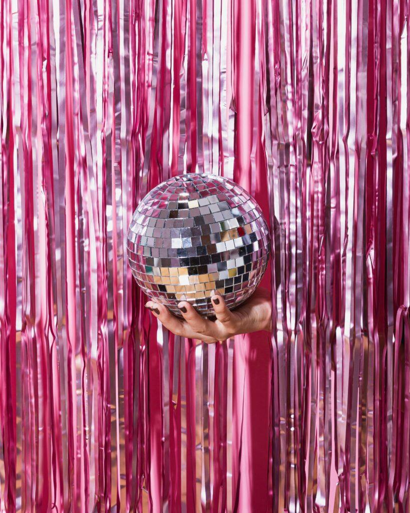 Eine Hand hält eine Diskokugel vor einen Vorhang aus pinken Fasern. Partystimmung: Der Drehbuchpreis Schleswig-Holstein ist wieder da!